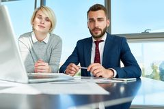 Young Business People Posing in Office. Portrait of handsome businessman and young women looking at camera during meeting while discussing work using laptop at Royalty Free Stock Photography