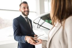 Handsome Car Salesman Giving Keys to Client. Portrait of handsome car salesman giving car keys to young women standing next to white shiny luxury car in Royalty Free Stock Photo