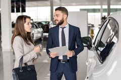 Handsome Car Salesman Talking to Client. Portrait of handsome car salesman talking to young women helping her choose luxury car  in showroom Stock Images