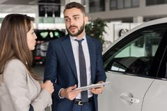 Handsome Car Salesman Consulting Client. Portrait of handsome car salesman talking to young women in car showroom helping her choose Royalty Free Stock Photo
