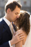Portrait of handsome caring groom hugging cute bride Stock Photos