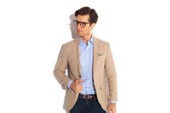 Portrait of handsome casual man wearing glasses. And fixing his jacket while posing looking away from the camera in isolated studio background Stock Photography