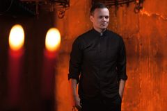 Portrait of handsome catholic priest or pastor with dog collar, dark red background. Stock Images
