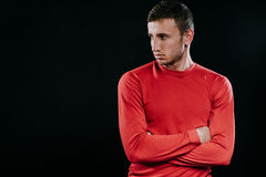 Portrait of handsome Caucasian sportsman wearing red sportswear and posing after exercises on dark background. Healthy inspiration. Caucasian sportsman wearing Royalty Free Stock Photo