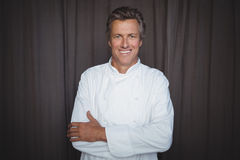 Portrait of handsome chef standing with arms crossed. In restaurant royalty free stock photography
