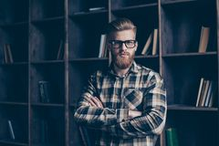Portrait of handsome clever brutal serious minded pensive though. Tful planning dreamy journalist standing with crossed arms in casual checkered shirt in front Royalty Free Stock Photos
