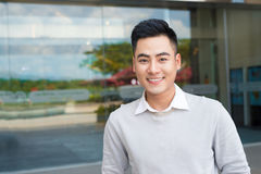 Portrait of an handsome confident asian man outside buidling. Royalty Free Stock Images
