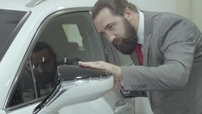 Portrait handsome confident bearded businessman in a business suit inspects newly purchased auto from the car dealership. Successful businessman inspects newly stock video