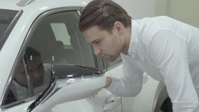Portrait handsome confident businessman inspects newly purchased auto from the car dealership. Car showroom. Advertising stock video