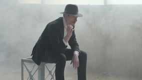 Portrait handsome confident man in a hat throws up and catches the coin sitting in an abandoned building. The head of stock video