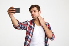 Portrait of a handsome confident man taking a selfie. While standing and posing isolated over white background stock photo