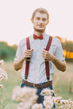 Portrait of handsome confident stylish man standing in field and looks into the camera Royalty Free Stock Photography