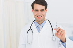 Portrait of a handsome doctor holding an injection Stock Photos