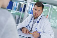 Portrait handsome doctor working at consultation royalty free stock photo