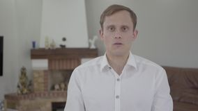 Portrait of handsome emotional blond man with amazing gray eyes in white t-shirt talking looking into the camera in the. Portrait of a handsome emotional blond stock footage