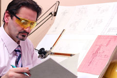 Portrait Of Handsome Engineer In Office. Adult caucasian male engineer examining documents. Focus on face Royalty Free Stock Images