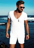 Fashion man model wearing white clothes posing on blue sea background stock photos