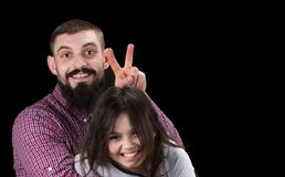 Portrait of handsome father and his cute daughter hugging, looking at camera and smiling royalty free stock image