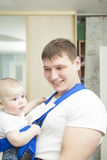 Portrait of handsome father holding son in sling Stock Photos