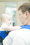 Portrait of handsome father holding son in sling Royalty Free Stock Photos