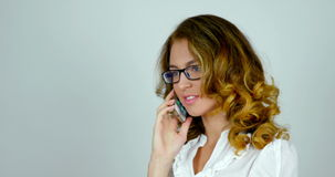 Portrait of a handsome female in her 20s talking on cellphone in studio. stock footage