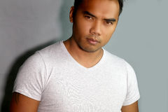 Portrait of a handsome Filipino. Next to a gray background royalty free stock photos