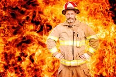 Fireman standing in front of wall of fire. Portrait of handsome fireman in uniform standing in front of wall of fire royalty free stock photos