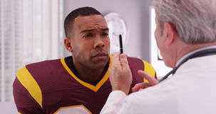 Portrait of handsome football player consulting sports injury wi. Th a doctor Stock Image