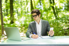 Portrait of young handsome freelance working at laptop at office table and talk at phone with costumer and make notice in green fo. Portrait of handsome stock photo