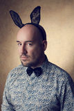 Portrait of a handsome glamourous bald bunny-man posing over gol Stock Images