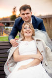 Portrait of handsome groom hugging beautiful bride sitting on be Stock Photography