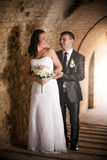 Portrait of handsome groom hugging bride at ancient tunnel Stock Photography