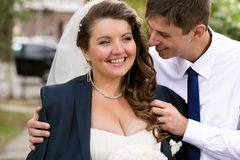 Portrait of handsome groom hugging chubby bride from back Royalty Free Stock Image