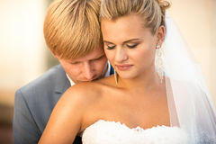 Portrait of handsome groom kissing blonde bride in shoulder Stock Photography