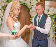 Portrait of handsome groom putting wedding ring on brides hand Stock Photo