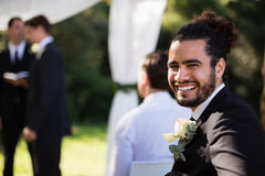 Portrait of handsome groomsman smiling in park. During wedding royalty free stock photography