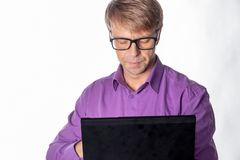 Portrait of handsome guy in casual shirt and glasses using laptop computer. Busy man working royalty free stock photo