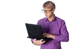 Portrait of handsome guy in casual shirt and glasses using laptop computer. Busy man working stock photo