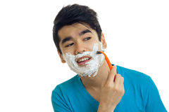 Portrait of a handsome guy with foam on his face that smiles and shaves his beard machine close-up Royalty Free Stock Photography