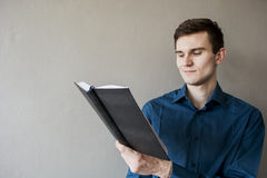 Portrait of a handsome guy looking away at a notebook. In a green shirt. Brunette with green eyes. On a monophonic gray background. He smiles slightly Royalty Free Stock Image