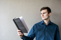 Portrait of a handsome guy looking away at a notebook. In a green shirt. Brunette with green eyes. On a monophonic gray background. He smiles slightly Stock Photo