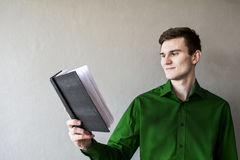 Portrait of a handsome guy looking away at a notebook. In a green shirt. Brunette with green eyes. On a monophonic gray background. He smiles slightly Stock Images