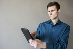 Portrait of a handsome guy looking away at the tablet. In a green shirt. Brunette with green eyes. On a monophonic gray background. Happy Young Man Using Stock Photos