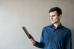 Portrait of a handsome guy looking away at the tablet. In a green shirt. Brunette with green eyes. On a monophonic gray background. Happy Young Man Using Royalty Free Stock Images