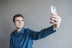 Portrait of a handsome guy looking into the camera with a phone in his hand. The guy makes self photo. In a green shirt. Brunette. With green eyes. On a Royalty Free Stock Photo