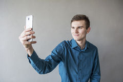 Portrait of a handsome guy looking into the camera with a phone in his hand. The guy makes self photo. In a green shirt. Brunette. With green eyes. On a Stock Photo