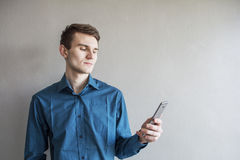 Portrait of a handsome guy looking to the side of the phone. In a green shirt. Brunette with green eyes. On a monophonic gray back. Ground. He smiles slightly Stock Photography