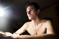 Portrait of a handsome guy with a naked torso. Photo of a close-up in a dark room and light from a lamp. Soft light. Green-eyed br. Unette full-face Royalty Free Stock Image