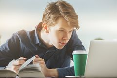 Portrait of handsome guy in office. Portrait of handsome guy working on project at modern desk with laptop, paperwork, supplies, coffee cup and other items Stock Photos