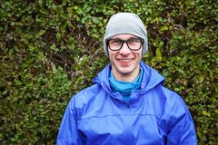 Portrait of handsome guy in sport clothes against green bush. Portrait of handsome young guy in sport clothes against green bush looking at camera and smiling Stock Photos
